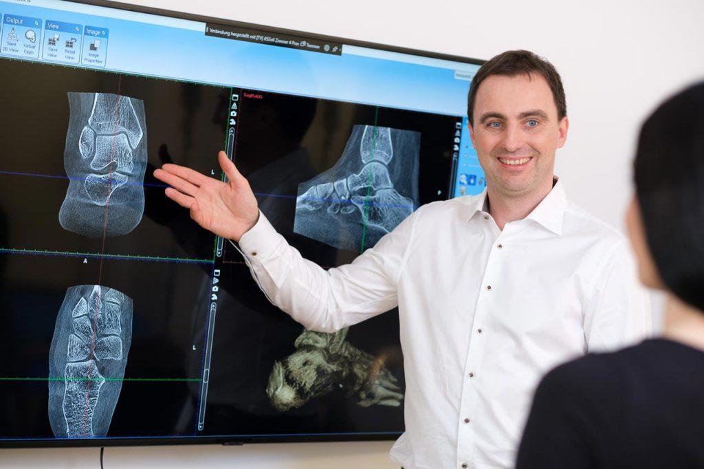 Dr. Stefan Böhr erläutert an einem großen Monitor die Röntgenbilder des Patienten