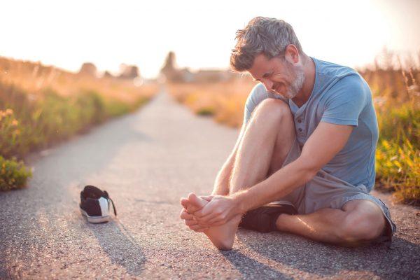 Läufer ist verletzt, hält sich den schmerzenden Fuß